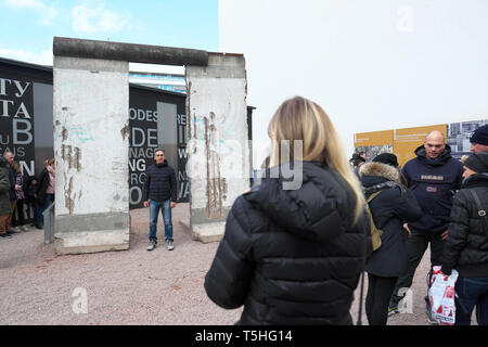 Berlin, Allemagne - touristes posent pour des photos à côté d'une section du mur de Berlin près de Checkpoint Charlie Banque D'Images