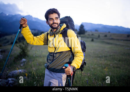Randonneur attrayant avec de gros sac à dos de voyage déménagement jusqu'à la piste de montagne et souriant Banque D'Images