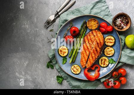 Saumon grillé avec légumes courgette, asperges, tomates, poivrons sur une plaque, fond gris. Haut de la vue, télévision jeter,copie espace. Banque D'Images