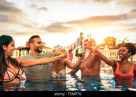 Groupe d'amis heureux de faire un pool party acclamer avec champagne au coucher du soleil - Les jeunes gens rire et s'amuser toasting with champagne Banque D'Images
