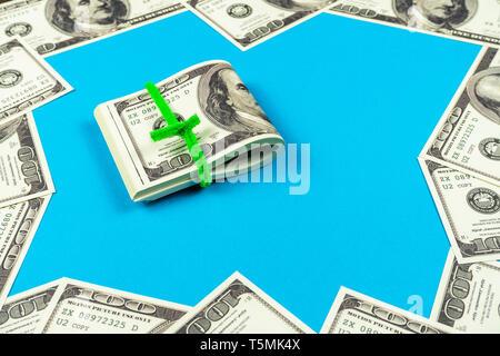 Dollar bills pliée en deux sur fond bleu clair