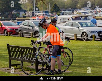 Deux cyclistes masculins obtenir leurs vélos route prêts à poursuivre leur voyage après avoir passé quelques minutes sur un banc en bois dans un parc public Banque D'Images