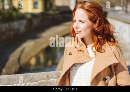 Introspection sérieuse jeune rousse femme debout dans le soleil du printemps dans un élégant manteau sur un pont sur un canal urbain Banque D'Images