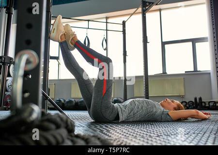 De grands progrès. Young Beautiful woman in sportswear doing stretching en face de la fenêtre à la salle de sport