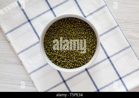 Les haricots mungo vert cru dans un bol blanc gris sur fond de bois. Mise à plat, les frais généraux, d'en haut. Banque D'Images
