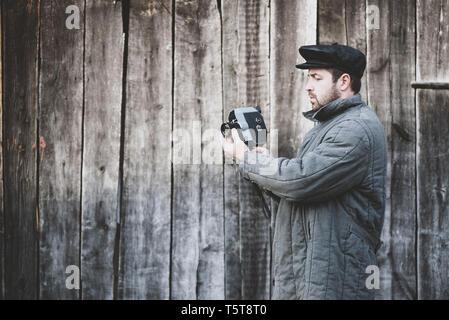 Caméraman à l'ancienne avec retro caméra dans les mains, effet mat. Concept - l'industrie du cinéma, film de 1970 Banque D'Images