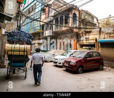 Homme Sikh marcher dans une rue étroite dans le vieux quartier de Delhi en Inde du Nord Banque D'Images