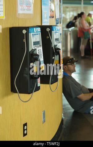 Un homme adulte appuyé contre payer l'écoute de sa station téléphone téléphone mobile, à Seattle, USA. Banque D'Images