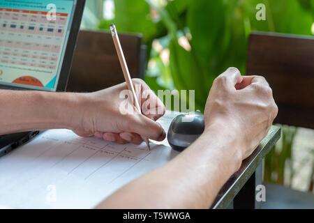 L'homme asiatique a écrit le budget avec un crayon dans la main gauche, côté à l'étude, à l'outdoor et feuille verte derrière. Banque D'Images