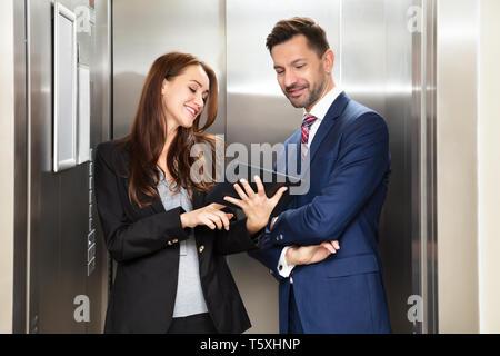 Smiling Young Young discuter lors de l'utilisation de tablette numérique, debout près de Ascenseur Banque D'Images