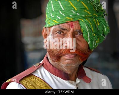 Garde de sécurité Indiennes âgées de henné du Rajasthan, teint en vert et les côtelettes de mouton amical turban Rajasthani (pagari) pose pour la caméra. Banque D'Images