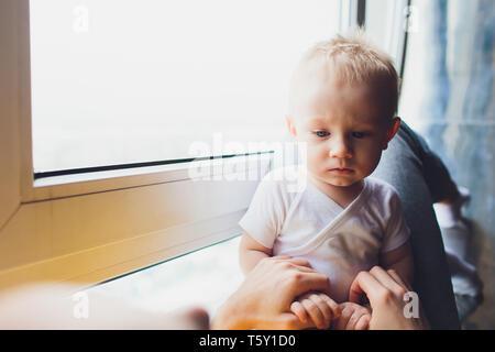 Mère jouant avec son bébé assis sur une fenêtre. Banque D'Images