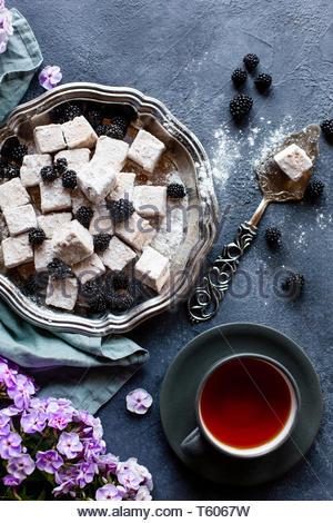 Dessert frais fait maison avec des baies sur plaque d'argent a servi avec le thé noir sur table béton. Mise à plat. Banque D'Images