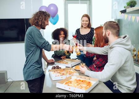 Jeunes amis manger une pizza et boire de la bière de s'amuser ensemble à la maison. Banque D'Images