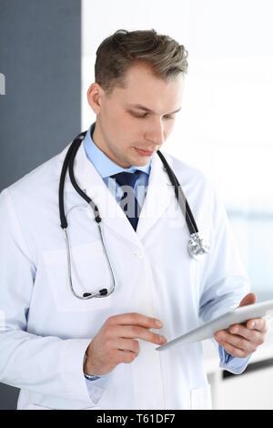 Docteur man using tablet computer de la recherche du réseau virtuel ou le traitement de la maladie. Perfect service médical en clinique. La médecine moderne, medic et données