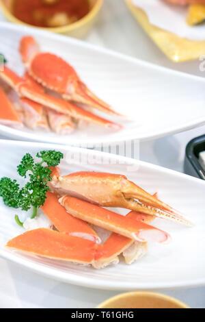 Close up et griffe japonaise à la vapeur sur la jambe du crabe blanc plat, décorer avec les légumes à côté. Banque D'Images