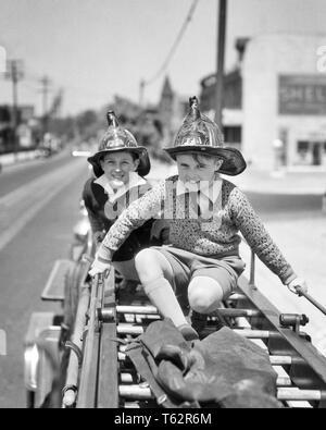 1930 TWO SMILING PRETEEN EXCITÉ GARÇONS EN CASQUES DE SÉCURITÉ POMPIER ASSIS ESCALADE ÉQUITATION JOUANT SUR L'ARRIÈRE D'un camion à incendie - b11918 HAR001 HARS UN JUSTE ÉQUILIBRE ENTRE LA SÉCURITÉ D'ÉQUIPE HEUREUX JOIE VITESSE COPIE CÉLÉBRATION VIE AMITIÉ ESPACE INSPIRATION pleine longueur risque mâles EXPRESSIONS CONFIANCE B&W CONTACT OCULAIRE FIREMAN RÊVES JOYEUX BONHEUR COURAGE FORCE AVENTURE EXCITATION CHOIX LOISIRS PUISSANT DE SPÉCIAL SUR LES PROFESSIONS OCCASION PRETEEN SMILES ÉCHAPPER IMAGINATION CONCEPTUELLE ÉLÉGANTE JOYEUSE CASQUES INHABITUELLE EXPÉRIENCE PASSIONNANTE MINEURS PRÉ-ADO PRÉ-ADO GARÇON L'UNITÉ NOIR ET BLANC Banque D'Images