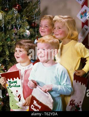 1960 PORTRAIT 4 ENFANTS FRÈRES ET SOEURS SMILING BY CHRISTMAS TREE MAINTENIR LES BAS WEARING PAJAMAS - kx3899 HAR001 FEMELLES HARS BROTHERS STUDIO SHOT SANTÉ ACCUEIL VIE COPIE Espace demi-longueur d'AMITIÉ PYJAMA Hommes frères soeurs BRUNETTE BONHEUR JOYEUX JOYEUX ET D'EXCITATION SŒUR SOURIRE CONNEXION Décembre 25 décembre F FRIENDLY COOPÉRATION JOYEUSE joyeuse convivialité la croissance des juvéniles de l'origine ethnique caucasienne VEILLE DE NOËL HAR001 old fashioned Banque D'Images