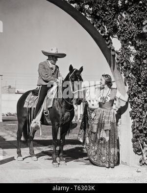1930 SMILING CAUCASIAN WOMAN IN TRADITIONAL COSTUME CHINA POBLANA PARLANT À L'HOMME HORSEACK MEXICAIN portant des vêtements COWBOY CHARRO - r11452 HAR001 HARS, HISTOIRE DE VIE RURAL FEMELLES COPIE ESPACE AMITIÉ Mesdames pleine longueur traditionnelle mexicaine TRANSPORT PERSONNES MÂLES B&W AMÉRIQUE DU NORD MEXIQUE AMÉRIQUE LATINE STYLES AVENTURE MODE ÉLÉGANT MID-ADULT MID-ADULT MAN WOMAN PORTRAIT NOIR ET BLANC DE L'ethnicité CHARRO CHINA POBLANA HAR001 ethnicité hispanique TOURISME ANCIENNE Banque D'Images