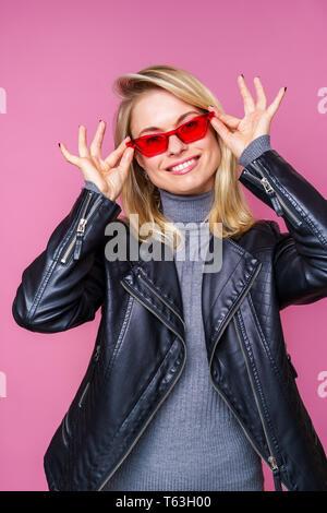 Photo de happy blonde à lunettes roses et blouson de cuir avec les mains près de visage Banque D'Images