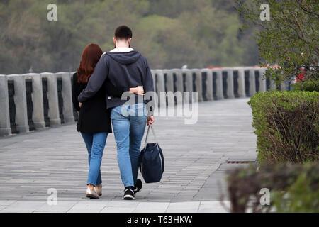 Couple in love hugging et balade dans un parc, vue arrière. Faire place au garçon et une fille sur date romantique, les gens en jeans, relation, sentiments réels