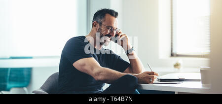 Smiling man at work on cell phone et travailler sur son laptop. Cheerful businessman working in office. Banque D'Images