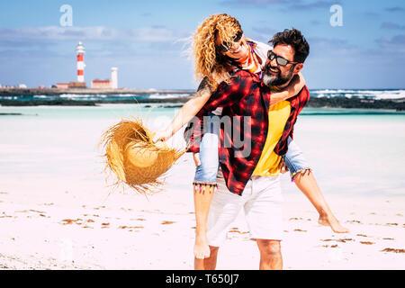 Les gens joyeux joyeux heureux couple jouant ensemble dans l'Amour avec homme portant femme en riant beaucoup s'amuser à la plage dans des vacances locations Banque D'Images