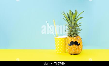 L'ananas mûr jaune avec une moustache noire verre pour verre jaune sur un fond bleu. Bouche d'une drôle de fruits tropicaux. Banque D'Images
