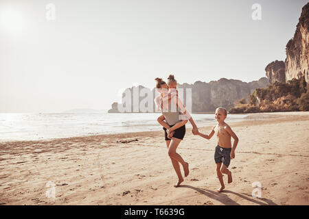 Mère rire usurpation de sa petite fille tout en courant avec son fils sur une plage pendant les vacances d'été Banque D'Images