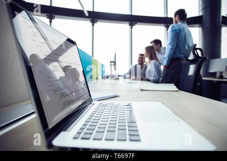 Close-up de travail dans un bureau moderne avec des gens d'affaires derrière. Collègues de travail pour discuter de leurs futurs plans financiers.