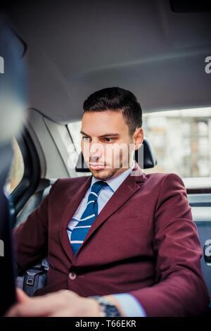 Businessman working on lap top pendant la conduite dans sa limousine Banque D'Images