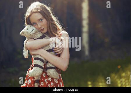 Portrait de tween sereine fille avec animal en peluche dans park Banque D'Images