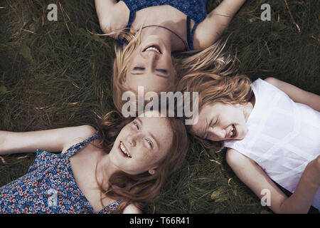 Portrait heureux sisters laying in grass Banque D'Images