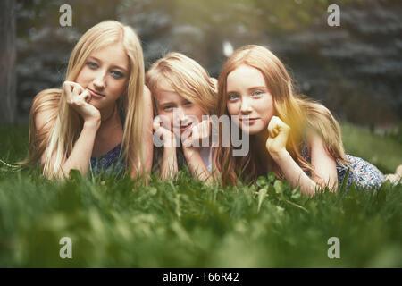 Magnifique Portrait sisters laying in grass Banque D'Images