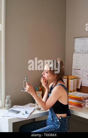 Young woman applying lip gloss dans mirror Banque D'Images