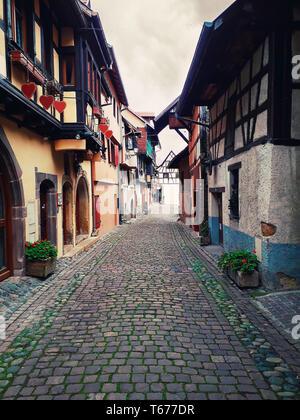 Ruelles de l'ancien village d'Eguisheim avec maisons médiévales à pans de bois le long de la célèbre route des vins en Alsace, France.