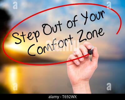 Man main écrit Étape hors de votre zone de confort avec marqueur noir sur l'écran visuel.