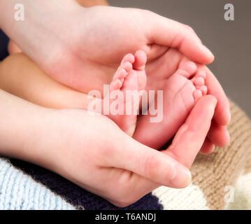 Nouveau-né de jambe petit bébé dans les mains de la mère Banque D'Images