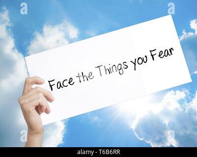Face à la crainte que vous inscrivez sur papier blanc. Tenir la main de l'homme papier avec texte. Isolé sur fond de ciel