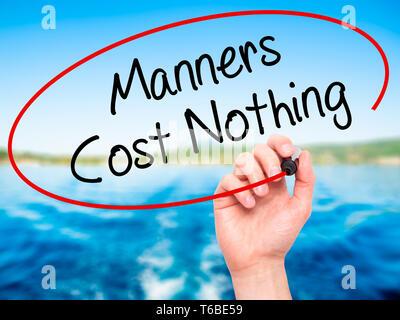 Man main écrit Manners Coût Rien avec marqueur noir sur l'écran visuel Banque D'Images