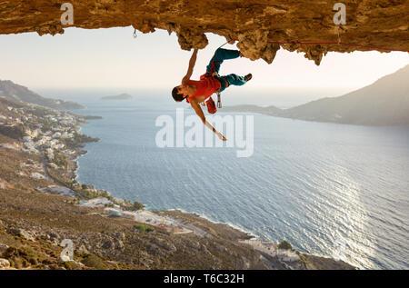 Caucasian male rock climber sur route difficile qui va de pair dans la grotte au plafond Banque D'Images
