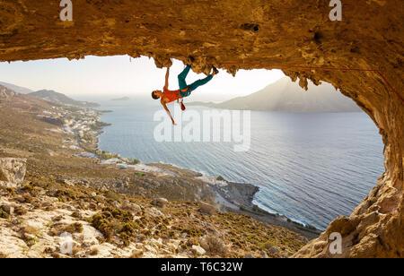 Male rock climber sur route difficile en longeant le plafond en cave, Kalymnos, Grèce Banque D'Images