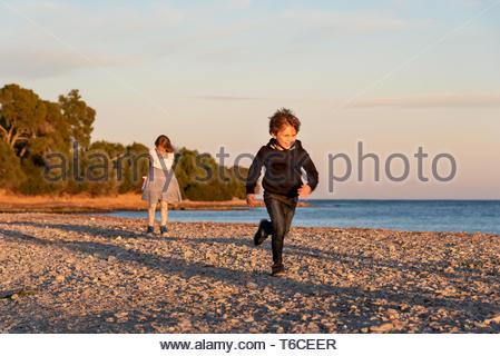 Siblings playing in a sunny Autumm coucher du soleil à la plage. Happy Young boy s'enfuit de sa sœur, alors qu'elle s'énerve. Banque D'Images