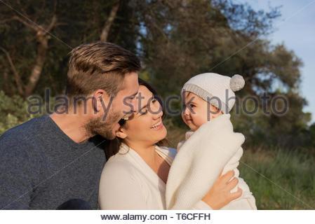 Les jeunes parents rire avec leur bébé, assis à l'extérieur dans une journée ensoleillée à forest et habillés en bleu et blanc Banque D'Images