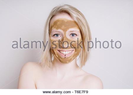Jeune femme avec terre de guérison ou d'argile beauté facial mask Banque D'Images