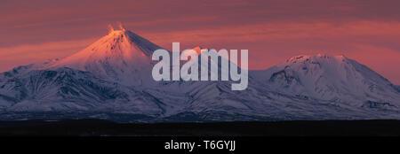 Superbe panorama hiver paysage de volcans du Kamtchatka au coucher du soleil: fumarolic (volcan Avachinsky activité gaz en éruption, cendres) et K Banque D'Images