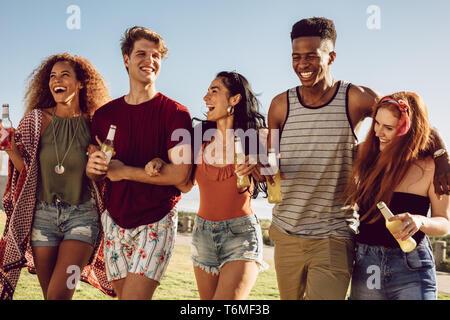 Groupe d'amis à marcher ensemble avec bras de verrouillage. Les jeunes, hommes et femmes, des bières à marcher ensemble et s'amuser. Banque D'Images