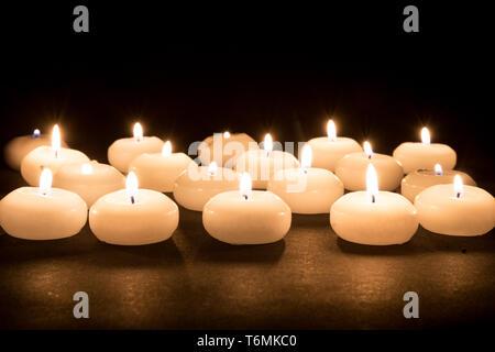 Plusieurs bougies blanches sur un fond noir Banque D'Images