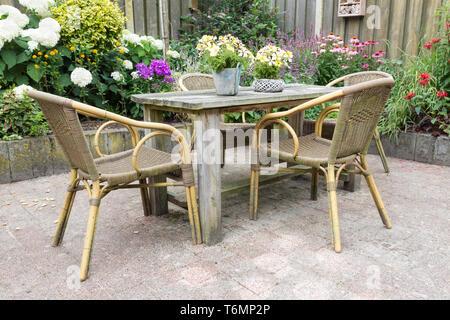 Table et chaises en bois dans un jardin d'ornement Banque D'Images