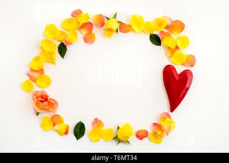 Cadre fait de roses, des pétales de rose et un cœur rouge, sur fond blanc. Banque D'Images